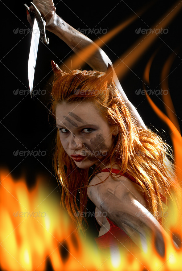 red devil girl with a knife in fire - Stock Photo - Images