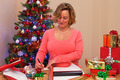 A woman at home wrapping Christmas presents - PhotoDune Item for Sale