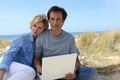 Couple on the dunes using laptop computer - PhotoDune Item for Sale