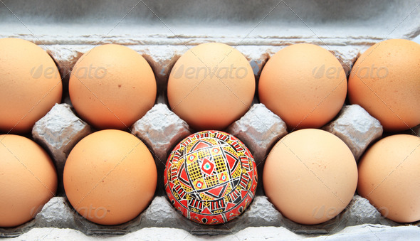 Easter egg in carton of brown eggs - Stock Photo - Images