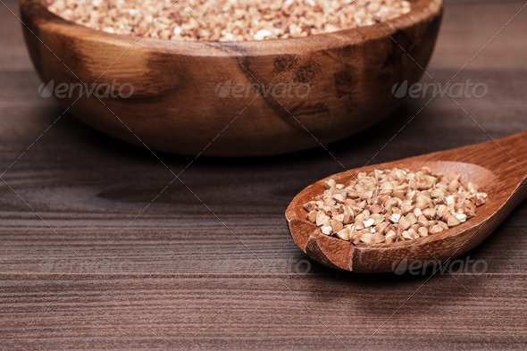 PhotoDune Plate And Spoon Full Of Buckwheat Over Wooden Background 3826779
