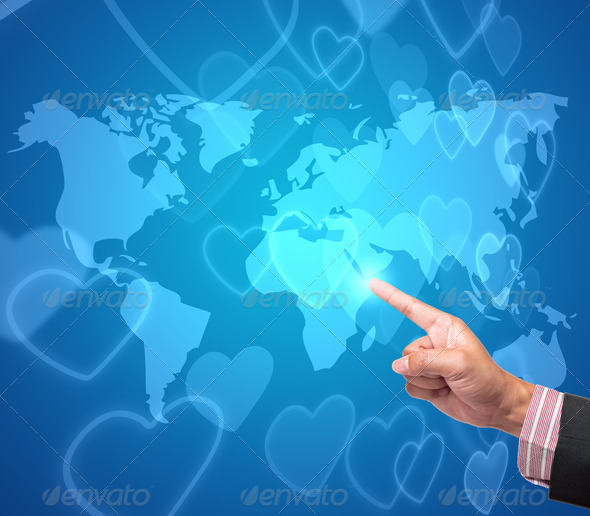 Hand pushing heart button on a touch screen interface - Stock Photo - Images