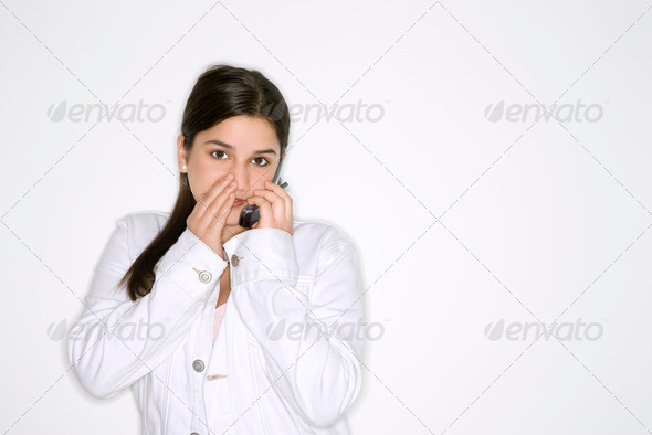 Girl whispering  into cellphone - Stock Photo - Images