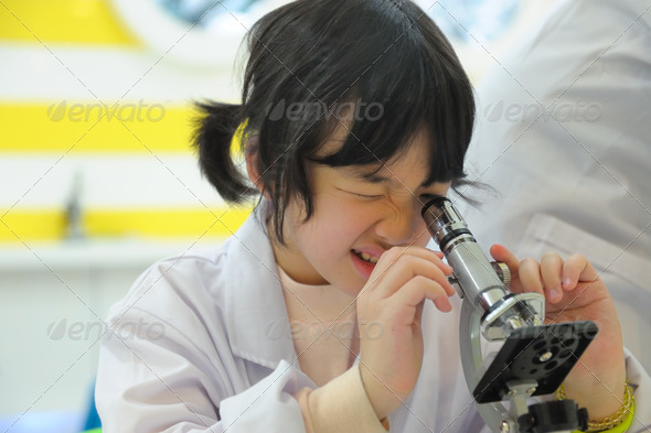 Asian kid looking into microscope - Stock Photo - Images