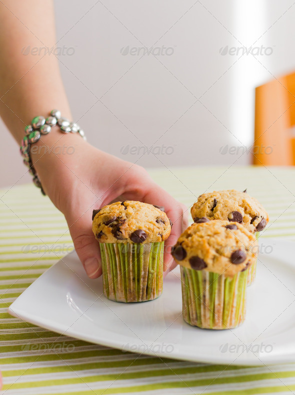 PhotoDune Nice girl hand taking chocolate chip muffin at breakfast 4112117