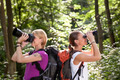two women hiking in forest and looking with binoculars - PhotoDune Item for Sale