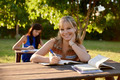 Young women studying with textbook for college exams at school - PhotoDune Item for Sale