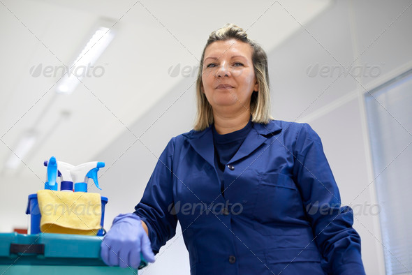 Portrait of happy professional female cleaner smiling in office - Stock Photo - Images