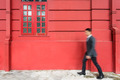 Busy business asian man walking past Red wall. - PhotoDune Item for Sale