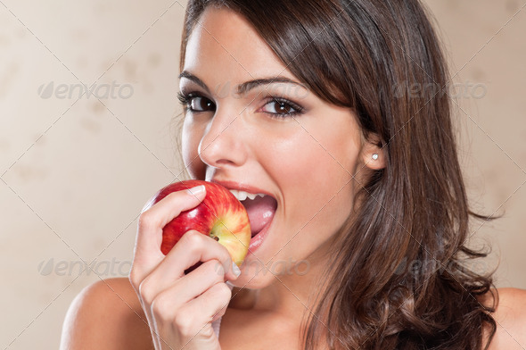 Pretty young woman eating an apple - Stock Photo - Images