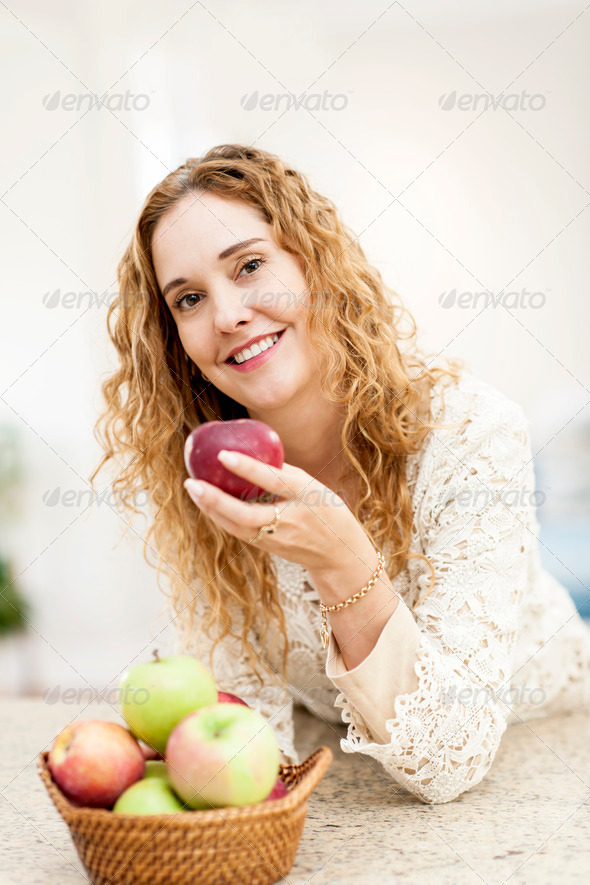 Smiling woman holding apple - Stock Photo - Images