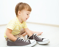 Boy is playing with big sneakers - PhotoDune Item for Sale