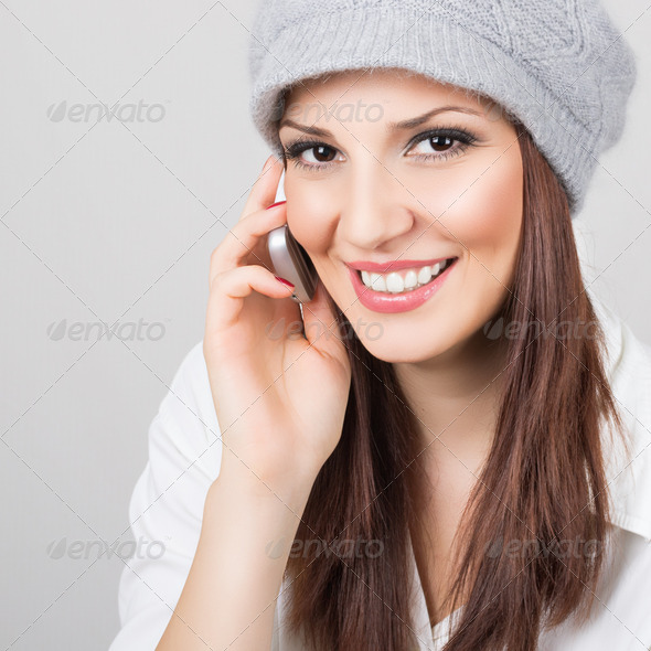 Cute young woman wearing hat talking on the phone - Stock Photo - Images