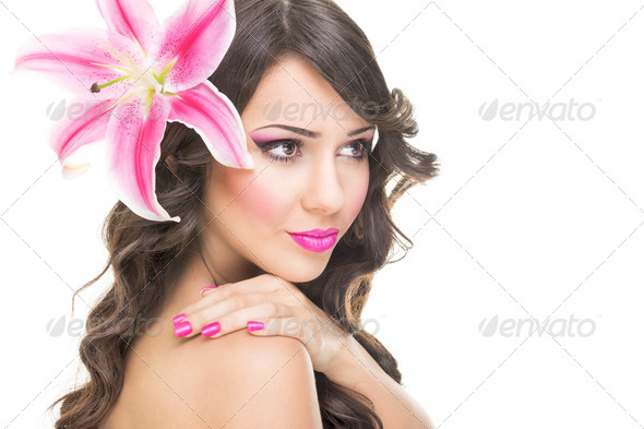 Beautiful face of young woman with pink lily flower - Stock Photo - Images