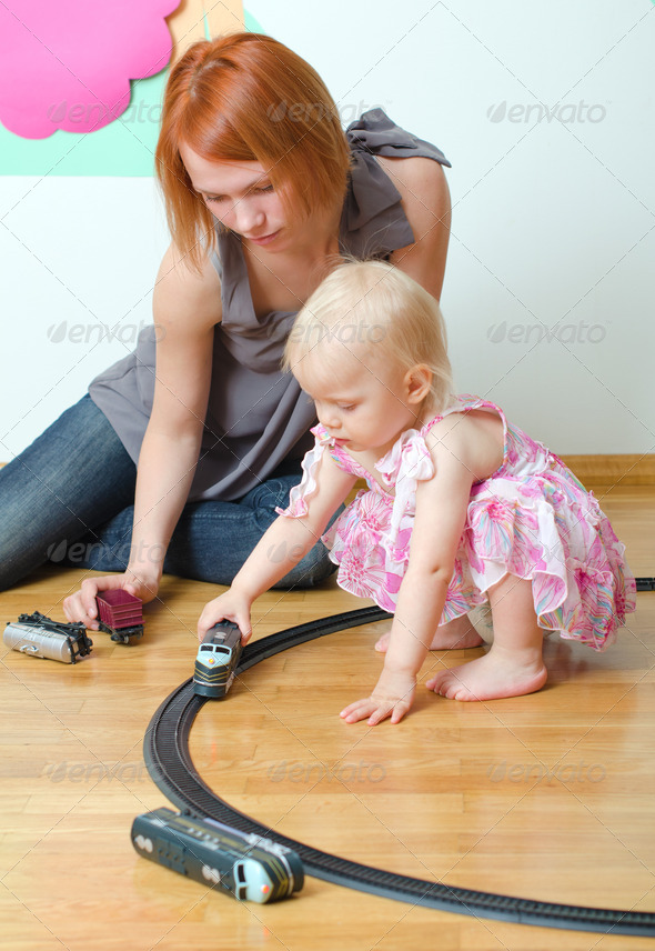 Little girl and her mother playing with railway sitting on the floor - Stock Photo - Images