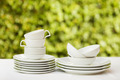 Clean Dishes And Cups On White Tablecloth On Green Background - PhotoDune Item for Sale
