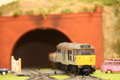 Model Railway Train Leaves Tunnel & Goes Through Level Crossing - PhotoDune Item for Sale