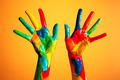 Painted hands, colorful fun. Orange background - PhotoDune Item for Sale