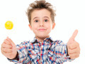 Little smiling boy shows thumb up with lollypop in hand - PhotoDune Item for Sale