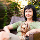 Beautiful woman in chair with little dog in garden - PhotoDune Item for Sale