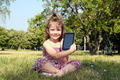 little girl with tablet sitting on grass - PhotoDune Item for Sale