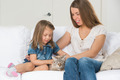 Mother and daughter sitting on sofa and cuddling cat - PhotoDune Item for Sale