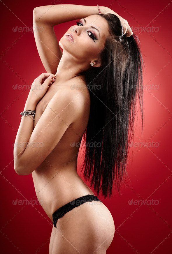 Hot brunette covering her breasts on red background - Stock Photo - Images