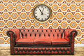Retro styled image of an old sofa and clock against a vintage wallpaper wall - PhotoDune Item for Sale