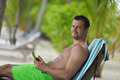 man ralaxing and use tablet at beach - PhotoDune Item for Sale