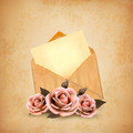 Three roses in front of an old envelope with a letter. Love letter concept.  - PhotoDune Item for Sale