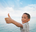 boy showing thumbs-up against sea - PhotoDune Item for Sale