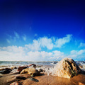 Waves hiting rocks on the sunny beach - PhotoDune Item for Sale