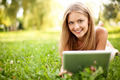 Young woman with digital tablet laying on grass - PhotoDune Item for Sale