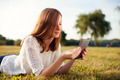 Beautiful young woman with digital tablet in park - PhotoDune Item for Sale