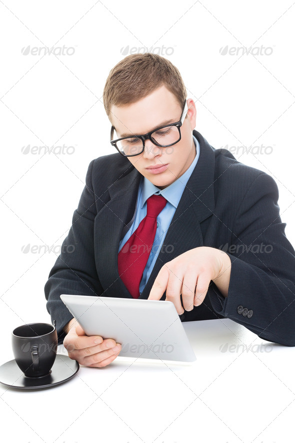 Young businessman wearing suit working on digital tablet - Stock Photo - Images