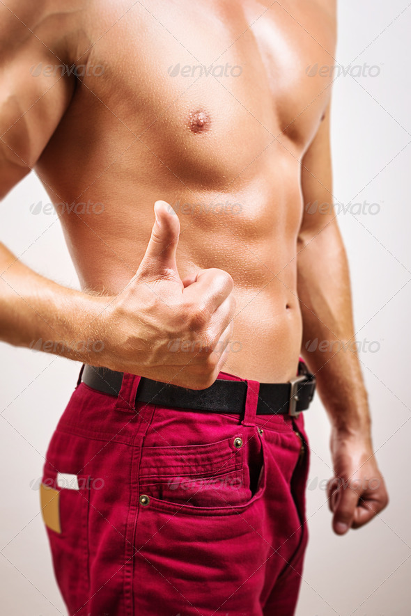 Handsome man happy about his body shape - Stock Photo - Images