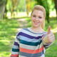 Portrait of beautiful girl holding thumbs up outdoors - PhotoDune Item for Sale