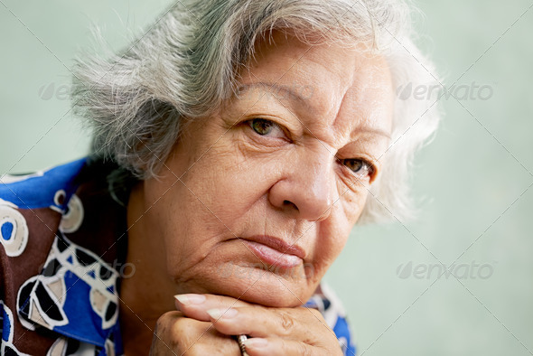 Portrait of serious old woman looking at camera with hands on ch - Stock Photo - Images