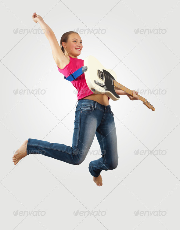 young woman playing on electro guitar and jumping - Stock Photo - Images