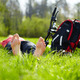 Barefoot biker enjoying relaxation lying in fresh green grass outdoors - PhotoDune Item for Sale