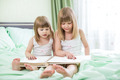Two little girls reading book sitting on bed - PhotoDune Item for Sale