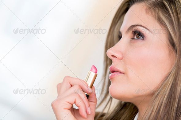 Woman applying lipstick - Stock Photo - Images