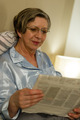 Relaxed smiling mature woman reading newspaper - PhotoDune Item for Sale