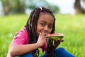 Outdoor portrait of a cute young black little girl eating waterm - PhotoDune Item for Sale