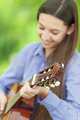 Smiling teenage girl playing guitar - PhotoDune Item for Sale