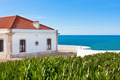 Turquoise sea, blue sky and white house in Portugal - PhotoDune Item for Sale