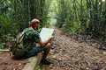 Travelling man sitting and looking at the map in the bamboo fore - PhotoDune Item for Sale