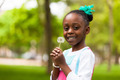 Outdoor portrait of a cute young black girl holding a dandelion - PhotoDune Item for Sale