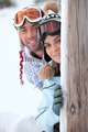young couple at ski resort hiding behind wooden post - PhotoDune Item for Sale