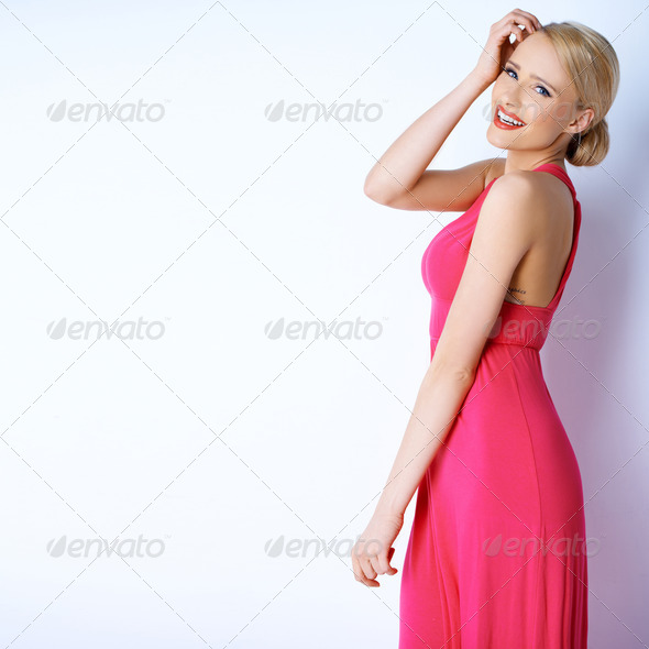 Gorgeous blond sexy woman posing in pink dress - Stock Photo - Images